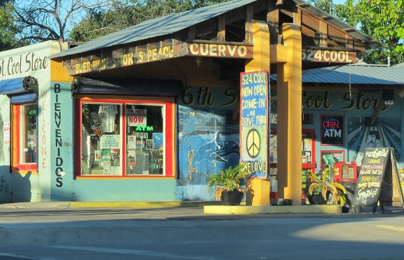 "The sign over a gayly painted convenience store in East Austin, Texas, reads, ""Beer, Wine, Smokes, Peace."" Photo by bf newhall"