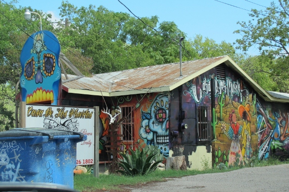 Graffiti and murals cover the Casa de los Muertos tatoo and head shop blows glass pipes on site. Austin TX. Photo by BF Newhall