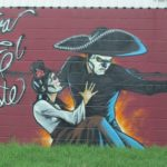 "A mural painted on a building in East Austin TX shows a man with sombrero and Spanish lady and the words, ""Viva el Este."" Photo by bf newhall"