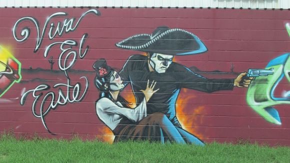 "A graffiti mural painted on a building in East Austin TX shows a man with sombrero and Spanish lady and the words, ""Viva el Este."" Photo by bf newhall"