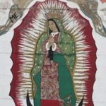 Detail of a grren, white and red mural depicting the Virgin of Guadalupe on the outer wall of a laundromat in East Austin , TX. Photo by BF Newhall.