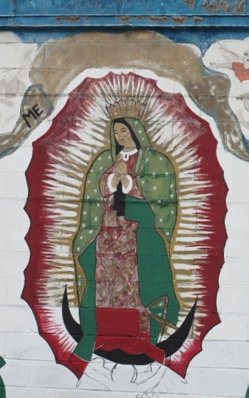 Detail of a grren, white and red mural depicting the Virgin of Guadalupe on the outer wall of a laundramat in East Austin , TX. Photo by BF Newhall.