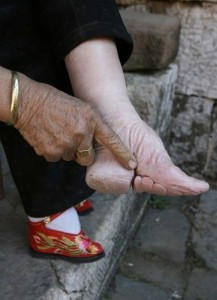 a chinese woman shows her bound foot.