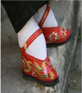 red embroidered shoe with strap on the bound foot of a Han Chinese woman.