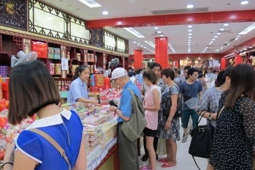 a single westerner  in a crowd of chinese shopper in a well-stocked candy story at Yu Gardens and Bazaaar in Shanghai.  Photo by BF Newhal