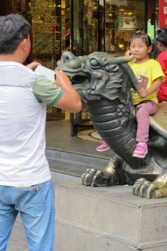 A man takes a photo of a small child sitting on a sculpture dragon in Shanghai's Yuyuan Bazaar. Photo by BF Newhall