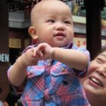 a pudgy faced chinese baby boy is held aloft by a woman who seems to be his grandmother in Shanghai. Photo by bf newhall
