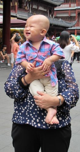 A baby in Shanghai smiles and looks towards his mother who is taking a photo of him. Photo by BF Newhall