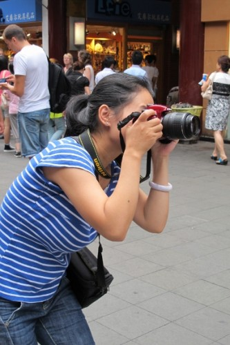 A woman in Shanghai aims her camera at her baby son. Photo by BF Newhall