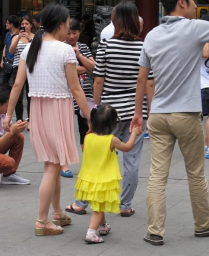 A couple walks hand-in-hand with their toddler in the streets of Shanghai. Photo by BF Newhall