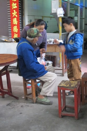 Grandparents in outdoor shop tend their grandchild in China. Photo by BF Newhal