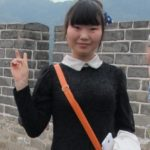A chinese girl in navy sweater and white collar gives the peace sign to foreigners on the GReat Wall. Photo by BF Newhall