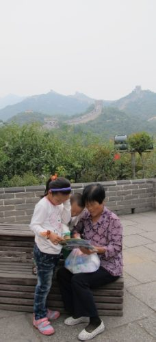 At the Great Wall of China an older woman tourist entertains two small children. Photo by BF Newhall
