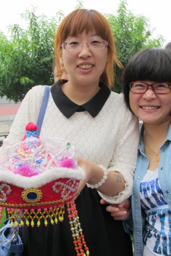 Two teenaged Chinese girls gettingt their picture taken in Beijing. One has dyed her hair orange.