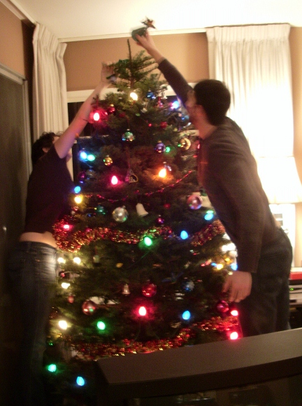Two young adults place the angel atop a green Christmas tree decorated with lights. Photo by BF Newhall