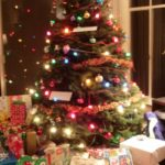 A live Christmas tree with lights, garlands and presents stacked underneath. Photo by BF Newhall