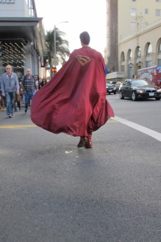 Actor Christopher Dennis dressed as Superman crosses Holllywood street cape billowing. Photo by BF Newhall