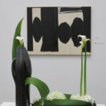 "An austere floral design of calas and leaves reflects Robert Motherwell's painting, ""At five in the Afternoon, 1950,"" at the Bouquets to Art show at the de Young. Photo by BF Newhall"