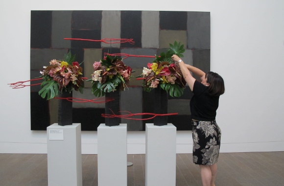 "Catherine Matsuyo Tompkison puts last touches on floral design reflecting Sean Scully's ""Wall of Light Horizon, 2005."" Photo by BF Newhall"