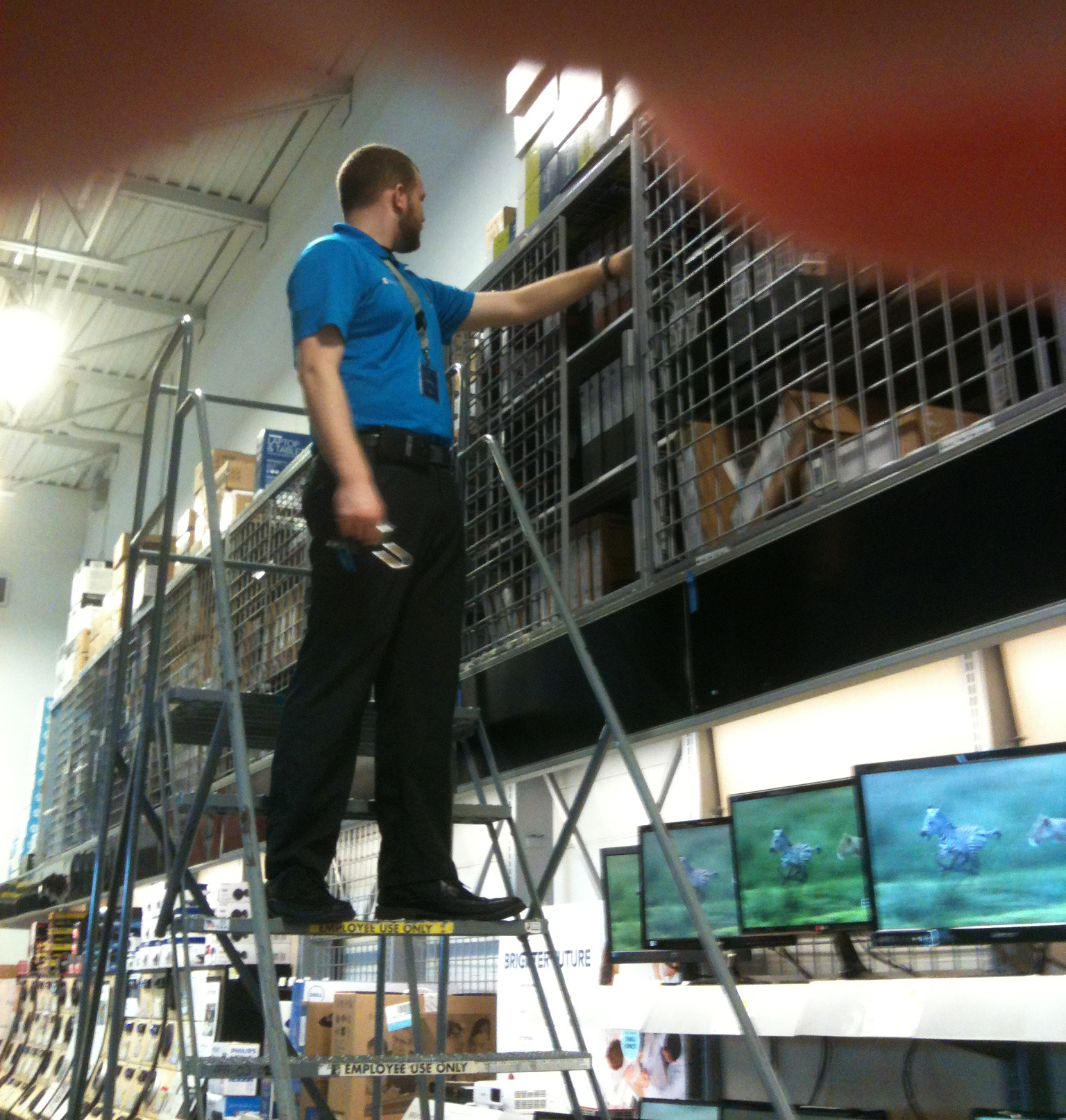 Sales clerk at Best Buy store climbs ladder to pull down a new Toshiba laptop for a customer. Photo by BF Newhall