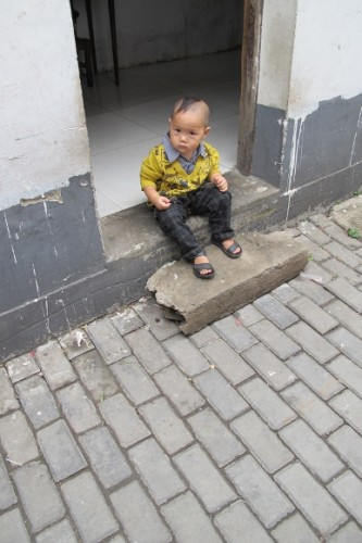 In Suchow, this little boy was set out on the doorstep of his house to pee, To expedite things, his pants were open at the crotch. I have preserved his dignity by retouching the photo to close up his fly. Photo by BF Newhall