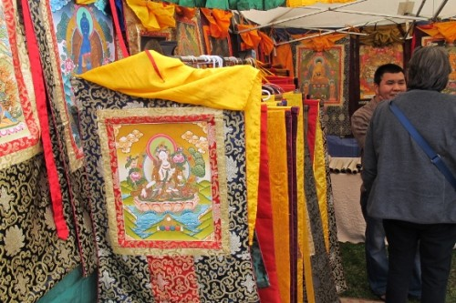 Kathmandu artist in his stall at Himalayan Fair Berkeley 2014 with dozens of thangkas from Nepal. Photo by BF Newhall