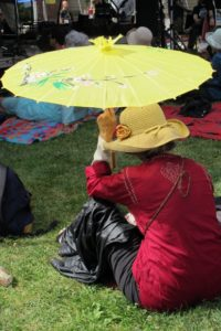 A woman in a red shirt sits in the sun at Berkeley's Himalayan Fair holding a yellow parasol over her head. Photo by BF Newhall