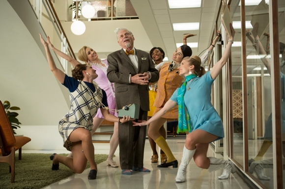 A scene from Mad Men TV series where Robert Morse playing Bert Cooper sings and dances surrounded by dancing secretaries for Don Draper.