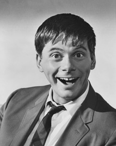 A black and white photo of actor Robert Morse as a young comedian gawking for the camera.