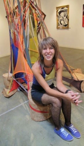 Hannah Woebkenberg sits in front of a large sculpture made with dyed pantyhose. Photo by BF Newhall