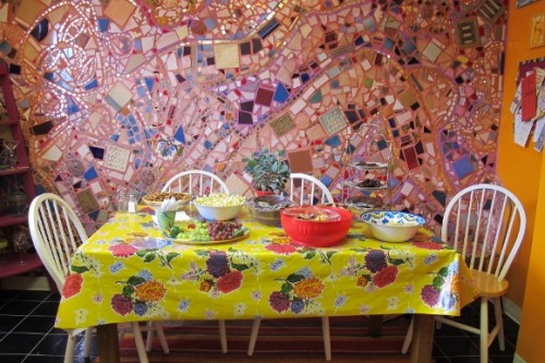 Food is served at Jingletown Art Studio on a table with flowered oilcloth tablecloth before a pink mosaic wall. Photo by BF Newhall