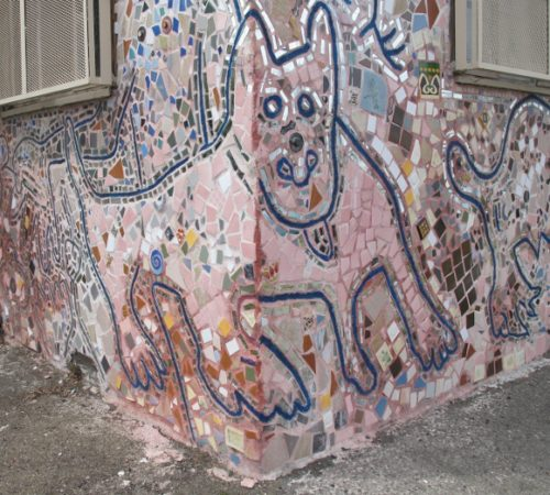 detail of pastel mosaic on facade of a building in Jingletown, Oakland, CA, showing body of dog wrapped around corner of building. Photo by BF Newhall