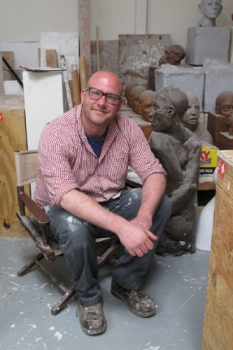 Christopher Kanyusik in his Oakland sculpture studio with his ceramic figures in background. Photo by BF Newhall