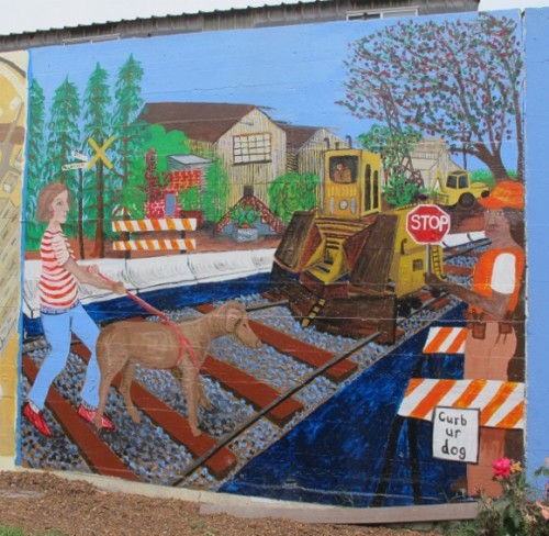 """Jingletown,"" a mural by Jill McLennan on the Rue de Merde, Jingletown, Oakland, CA. It shows a woman walking her dog. Photo by BF Newhall"