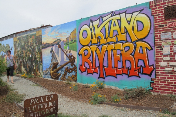 "First panel of the murals along Rue de Merde in Jingletown, an Oakland, CA, neighborhood is by Bill Silveira. It shows the words ""Oakland Riviera."" Photo by BF Newhall"