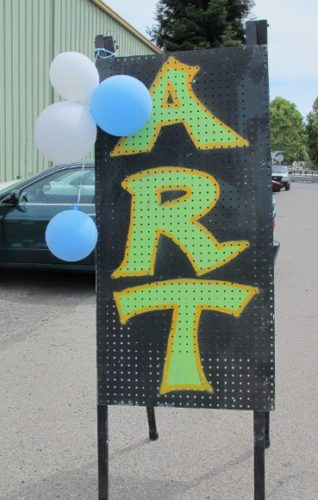 "Bright green letters spell out the word ""art"" on a black background on a sign for East Bay Open Studios. Photo by BF Newhall"