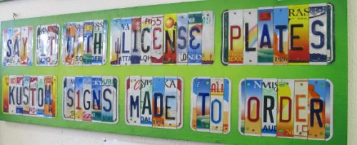 """Bill Silveira cut up US license plates to make a sign reading """"Kustom Signs Made to Order. Photo by BF Newhall"""". Photo by BF Newhall"""