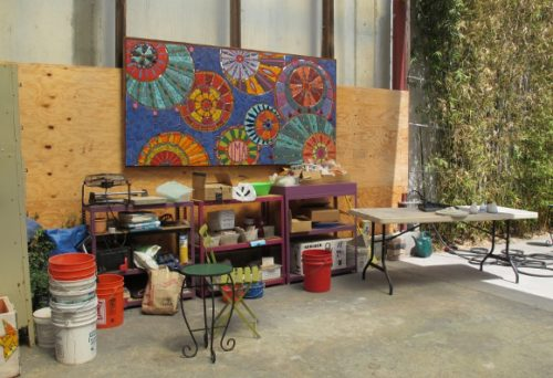 The workroom of the Iinstitute of Mosaic Art, Berkeley, CA, with open garage door and mosaic by Laurel True's 2013 summer mural class. Photo by BF Newhall