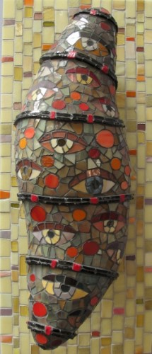 "A three-dimensionalgreenish mosaic, ""Gazing Cocoon,."" by Wilma Wyss on display at the Institute of Mosaic Art, Berkeley, represents a cocoon with eyeballs looking out. Photo by BF Newhall"