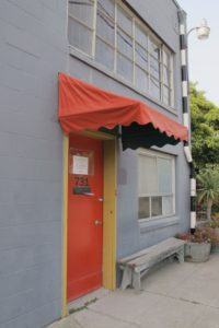 The entrance to the gray Berkeley Potters Guild building is a red door with red awning. Photo by BF Newhall