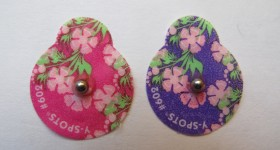 Two pear-shaped floral skin markers with metal beads for marking nipples during mammogram. Photo by BF Newhall