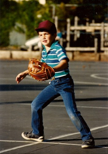 A 6-year-old boy in jeans and T-shirt with catcher's mitt goes for the catch. Photo by BF Newhall