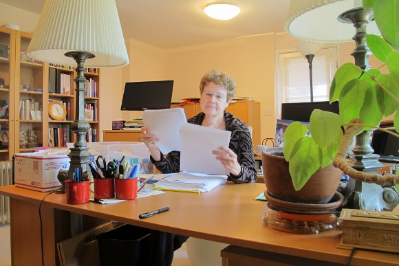 "Barbara Falconer Newhall in her San Francisco Bay Area writing room with desk and bookcases editing the paper print-out of her book manuscript, ""Wrestling with God."" Photo by Barbara Newhall"