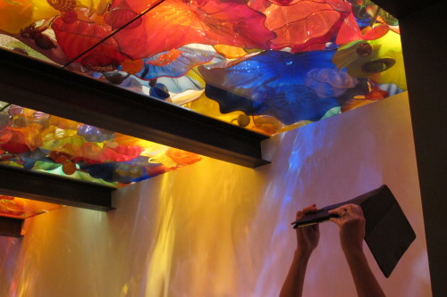 A museum-goer uses an etablet to photograph the colorful ceiling of Dale Chihuly's Sealfe Room at the Chihuly Garden and Glass museum in Seattle. Photo by Barbara Newhall