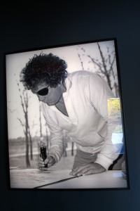 A black and white photo of glassblower Dale Chihuly at work hangs in the the Chihuly Garden and Glass museum in Seattle.