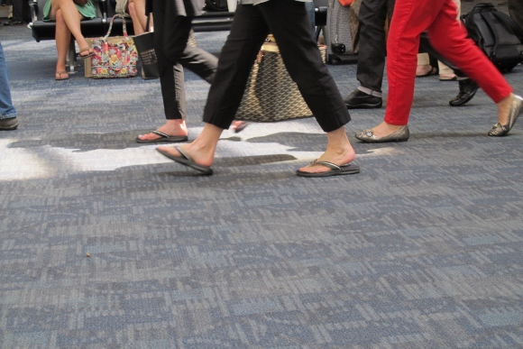 We see the feet of passengers rush to and from Delta Air flights at SFO.