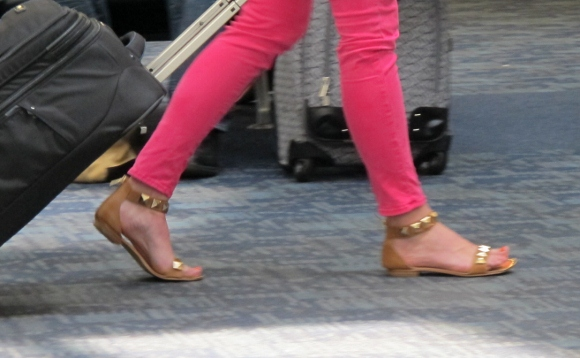 A woman wearing gold sandals and tight pink leggings pulls a carry-on at SFO airport. Photo by Barbara Newhall