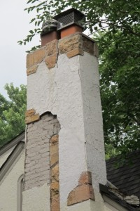 The stucco has fallen away from the chimney on a Tudor bungalow in Minneapolis, revealing the brick work underneath. Photo by Barbara Newhall