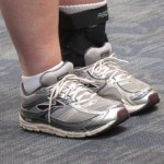 A girl at SFO wears cross trainers and a brace on her ankle. PHoto by Barbara Newhall
