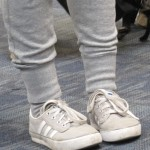 A pigeon-toed girl at SFO wears gray tights and white sneakers, her toes pointed in. Photo by Barbara Newhall